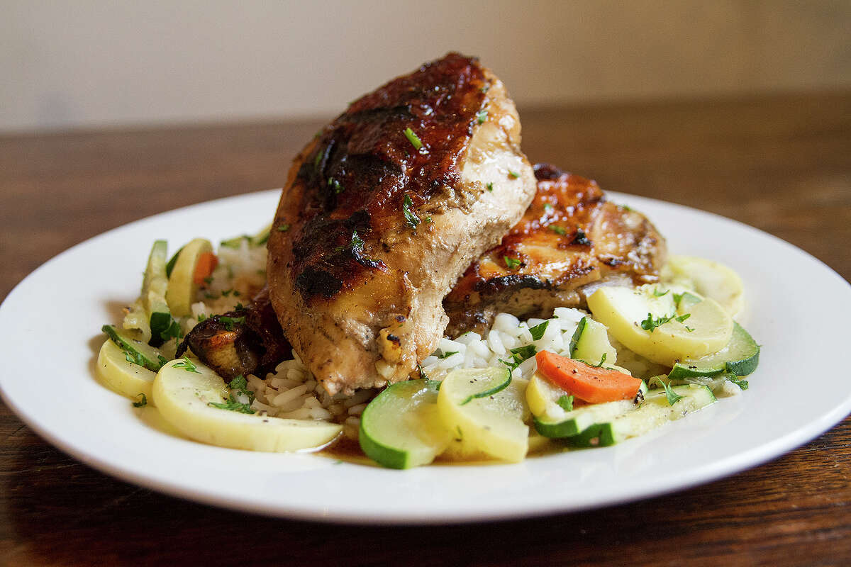 A dinner item of roasted chicken is served on a bed of rice pilaf with a veggie medley of squash, zucchini and carrots.