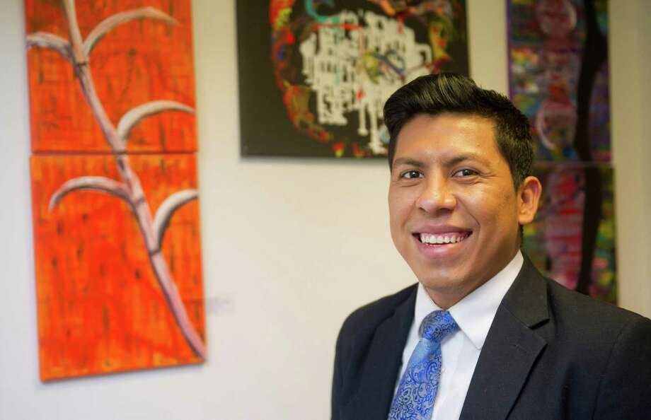 Rene Soto poses for a photo in his Stamford office as his artwork, and artwork by artists he promotes, hangs behind him on Thursday, November 6, 2014. Photo: Lindsay Perry / Stamford Advocate
