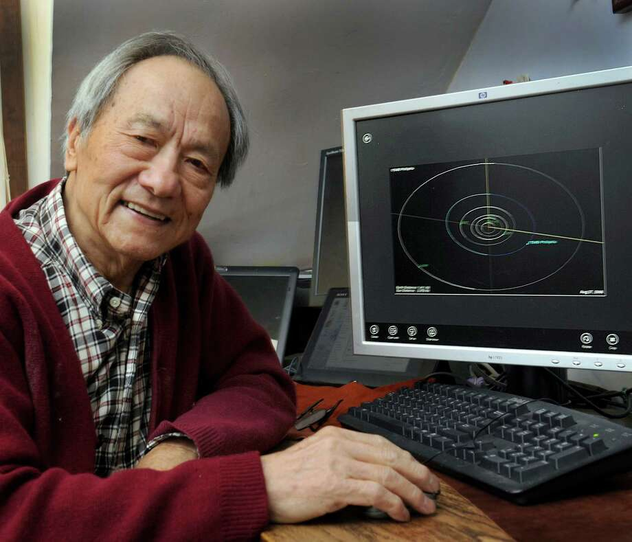 Dr. Phillip Lu, a retired professor of astronomy at Western Connecticut State University, recently had a minor planet named after him - 175450 Phillipklu.  Lu is photographed in his Danbury home next to a computer image that shows the planet, Thursday, Nov. 6, 2014. Photo: Carol Kaliff / The News-Times
