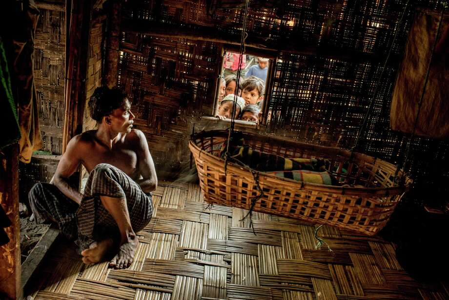 Mahmud, 24, cares for his son as children watch from a window at a camp full of Rohingya refugees on the edge of Sittwe, Burma. Photo: TOMAS MUNITA / New York Times / NYTNS