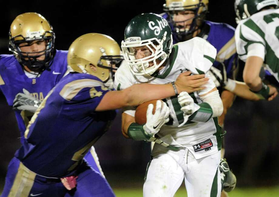 Shen's Willy Stevenson, center, carries the ball as CBA's Dom Herald defends during their football game on Friday, Sept. 19, 2014, at Christian Brothers Academy in Colonie, N.Y. (Cindy Schultz / Times Union) Photo: Cindy Schultz / 00028643A