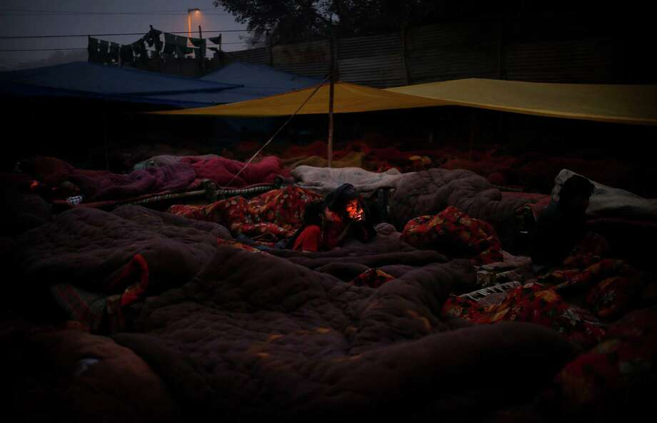 A homeless man lights up a cigarette after waking up on a rented bed at a poor neighborhood in New Delhi, India, Wednesday, Jan. 15, 2014. Beds on a cot with blankets cost  approximately $.50 while a bed on the ground with blankets cost $.15 per day. (AP Photo/Saurabh Das) Photo: Saurabh Das / ASSOCIATED PRESS / ONLINE_CHECK