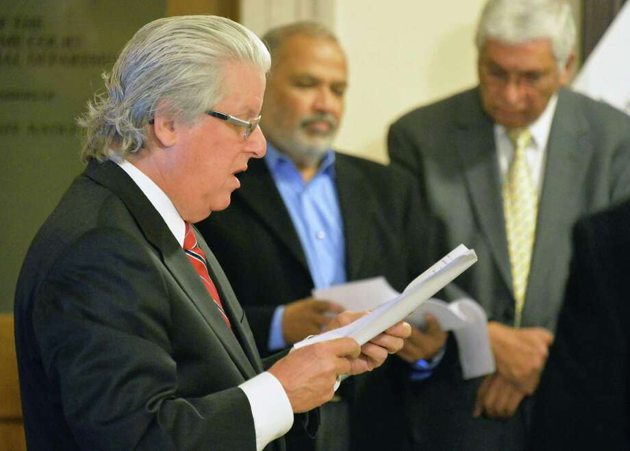 Attorney Terrance Christenson ,left, presides over the auction of the Holiday Inn on Wolf Road at the Albany County Courthouse Thursday Nov. 6, 2014, in Albany, NY.  (John Carl D'Annibale / Times Union) Photo: John Carl D'Annibale / 00029359A