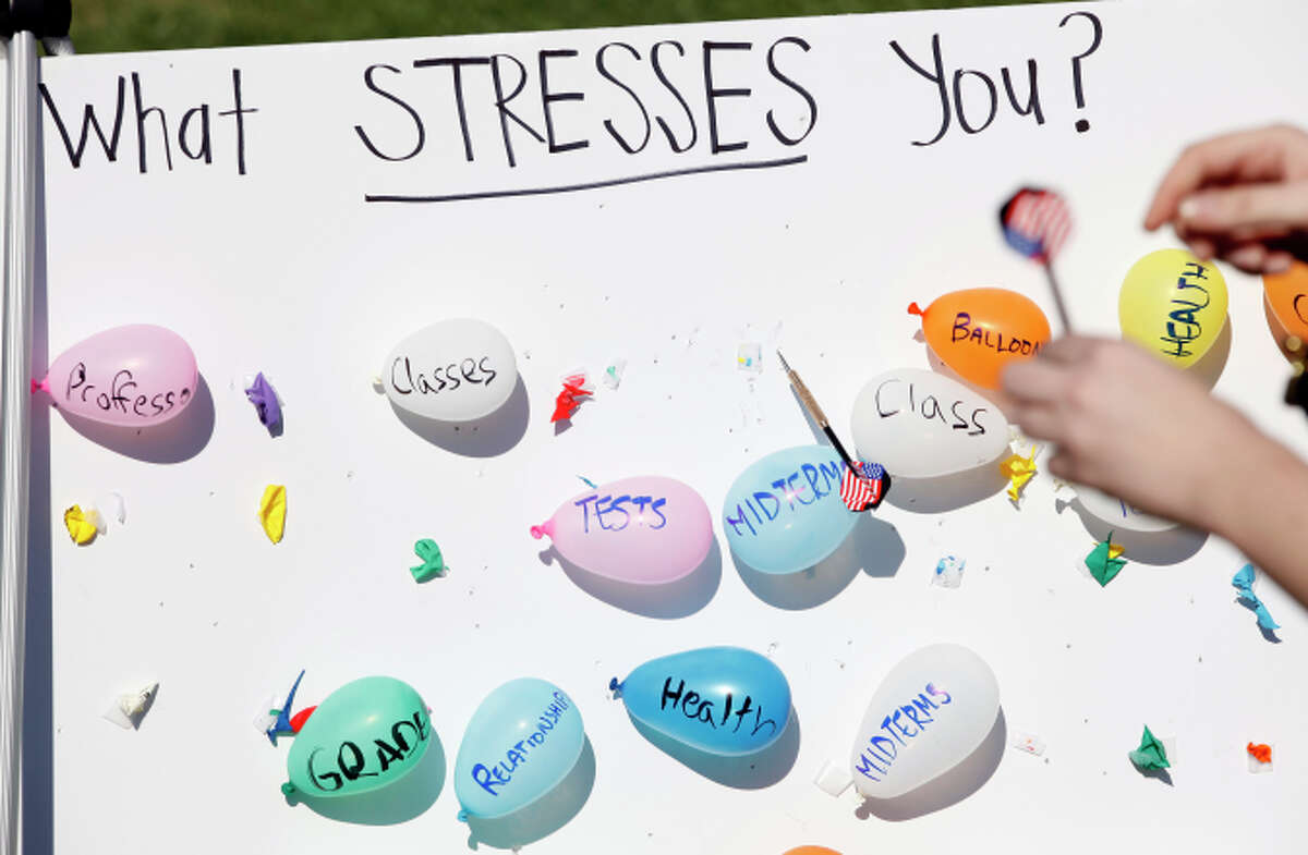 A student participates in an event designed to call attention to stress and mental health on Memorial Glade at UC Berkeley on Nov. 6, 2014. Students could throw darts at pre-written stressors or write their own on balloons.