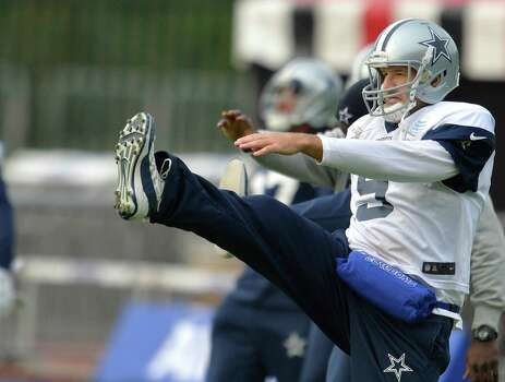 Cowboys quarterback Tony Romo does some stretching exercises before Thursday's practice. Romo, who didn't play in last Sunday's loss to the Cardinals because of his third back injury in 18 months, is optimistic he'll play in Sunday's game against the Jaguars in London. Photo: Sean Ryan / Sean Ryan / Associated Press / NFL UK