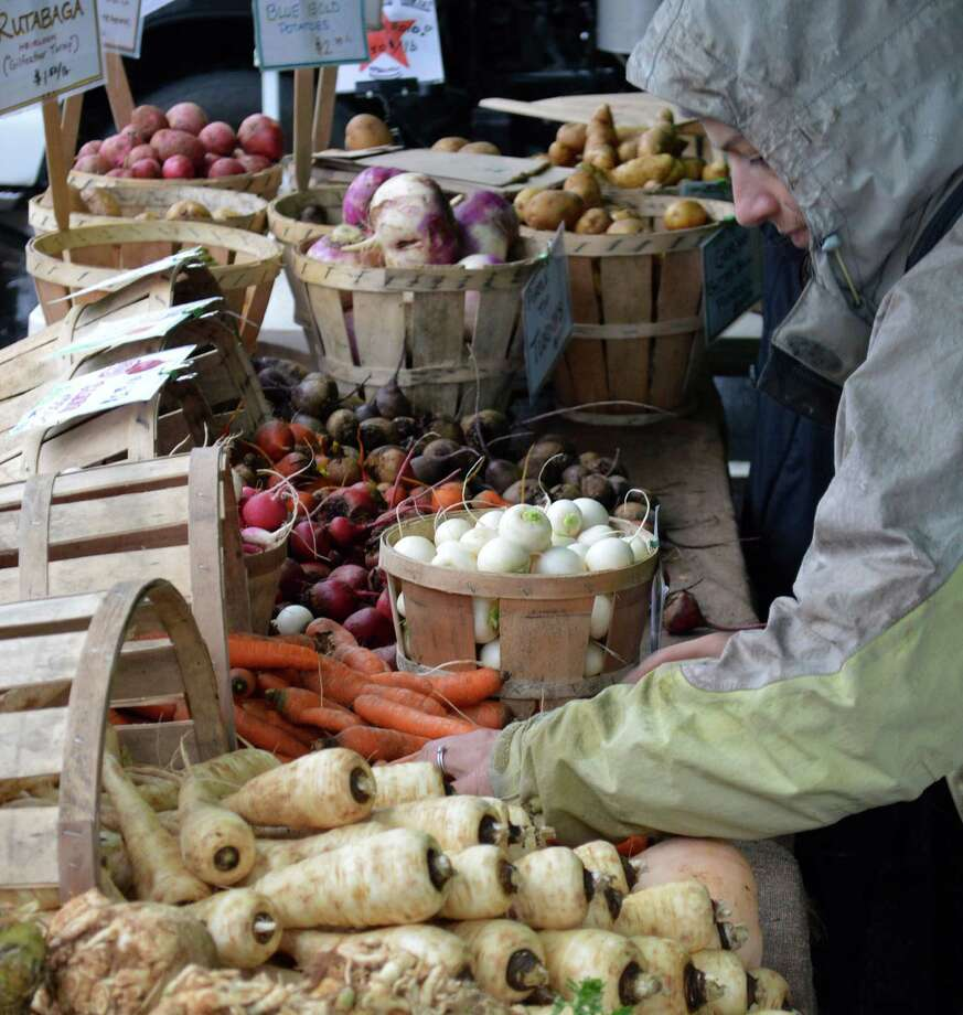 Rebecca Batchie of Fort Hill Farm in New Milford restocks root vegetables at the Westport Farmers Market last outdoor session Thursday, before it moves to the winter market venue Nov. 15. Photo: Jarret Liotta / Westport News