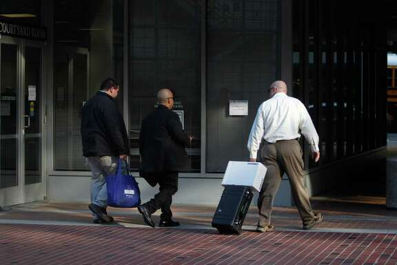 Representatives with the California Attorney General's office carry a bag and rolling case with a box as they leave the California Public Utilities Commission offices on Thursday, November 6, 2014 in San Francisco, Calif.