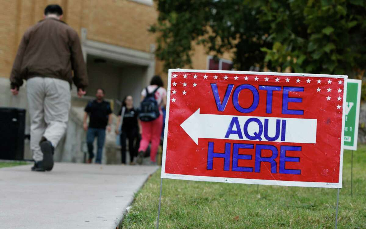 A sign shows the way to the poll Tuesday in Austin. Democrats say they should have done a better job mobilizing the Latino vote. Republicans point to Governor-elect Greg Abbott's strong Latino support.