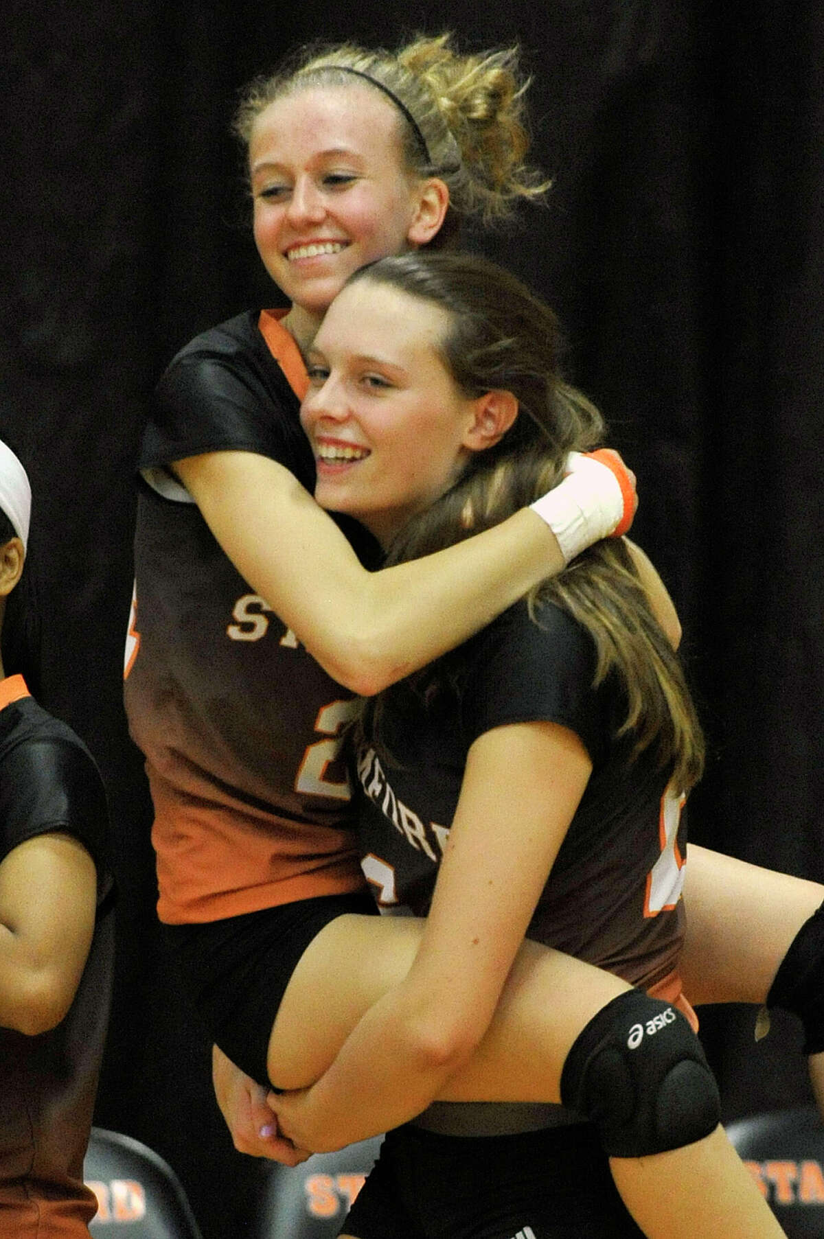 Stamford's Cali Schenkel carries her team mate Liisa Balazs after beating Greenwich, 3-2, in their Class LL second round playoff volleyball match at Stamford High School in Stamford, Conn., on Thursday, Nov. 6, 2014.