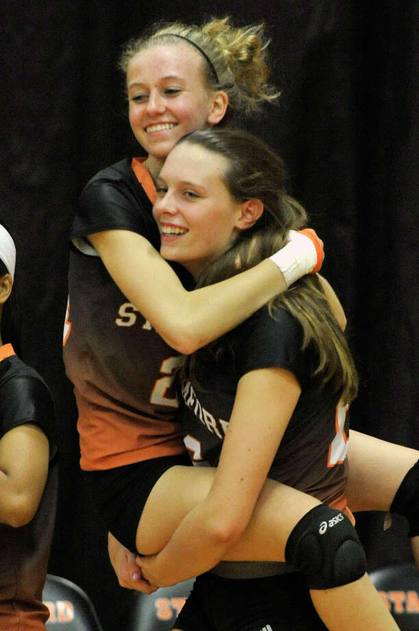 Stamford's Cali Schenkel carries her team mate Liisa Balazs after beating Greenwich, 3-2, in their Class LL second round playoff volleyball match at Stamford High School in Stamford, Conn., on Thursday, Nov. 6, 2014. Photo: Jason Rearick / Stamford Advocate