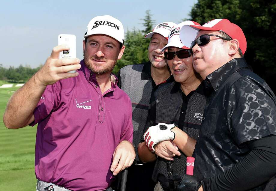 SHANGHAI, CHINA - NOVEMBER 05:  Graeme McDowell of Northern Ireland takes a 'Selfie' with his team during the pro am event prior to the WGC - HSBC Champions at the Sheshan International Golf Club on November 5, 2014 in Shanghai, China.  (Photo by Ross Kinnaird/Getty Images) ORG XMIT: 517278677 Photo: Ross Kinnaird / 2014 Getty Images