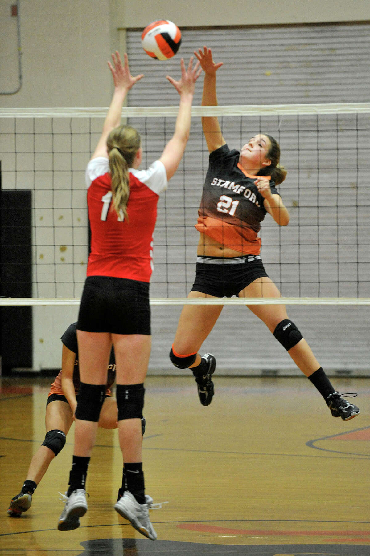 Stamford's Anne Eilertsen spikes the ball while Greenwich's Abigail Wolf attempts to block the shot during their Class LL second round playoff volleyball match at Stamford High School in Stamford, Conn., on Thursday, Nov. 6, 2014. Stamford won, 3-2.