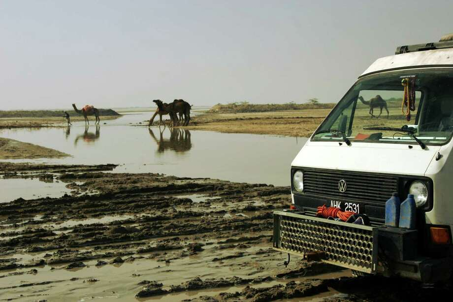 A group of camels sip water and watch the silly humans and their wheeled machine stuck in the mud. Pakistani border, Gujarat, India. Photo: Brad And Sheena Van Orden, Drive Nacho Drive / Drive Nacho Drive