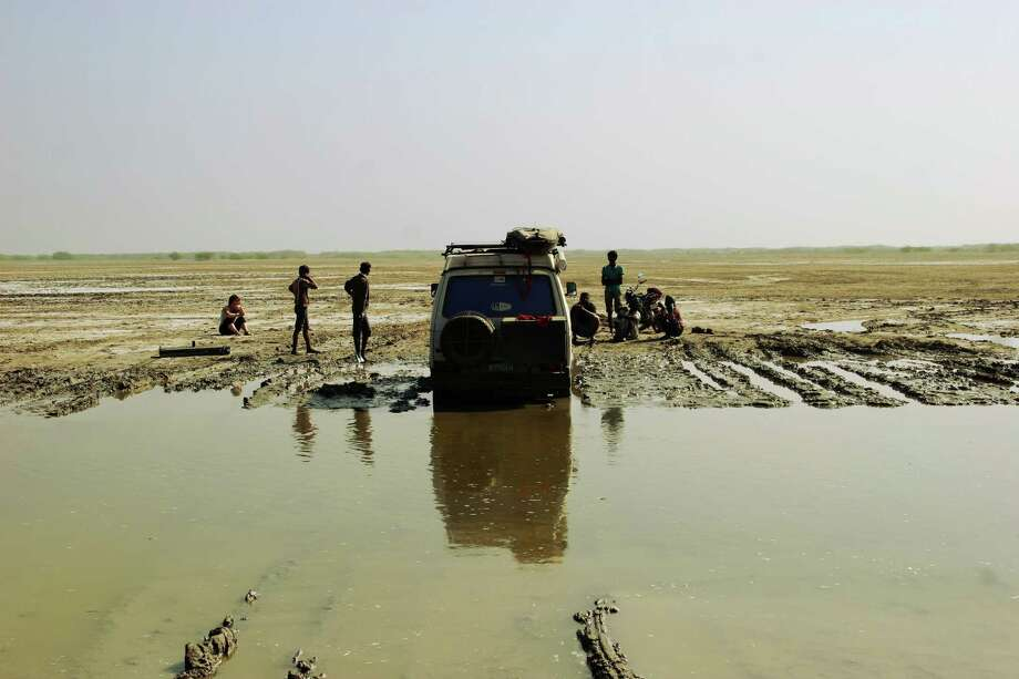 During their day-long drive without a road along the Pakistani border, Brad attempts a river crossing and fails, proving that water and clay combine to form an insurmountable obstacle for Nacho's two-wheel-drive. Soon a group of men emerge out of nowhere with a bucket of peanuts and nothing else to do but sit and watch. Photo: Brad And Sheena Van Orden, Drive Nacho Drive / Drive Nacho Drive