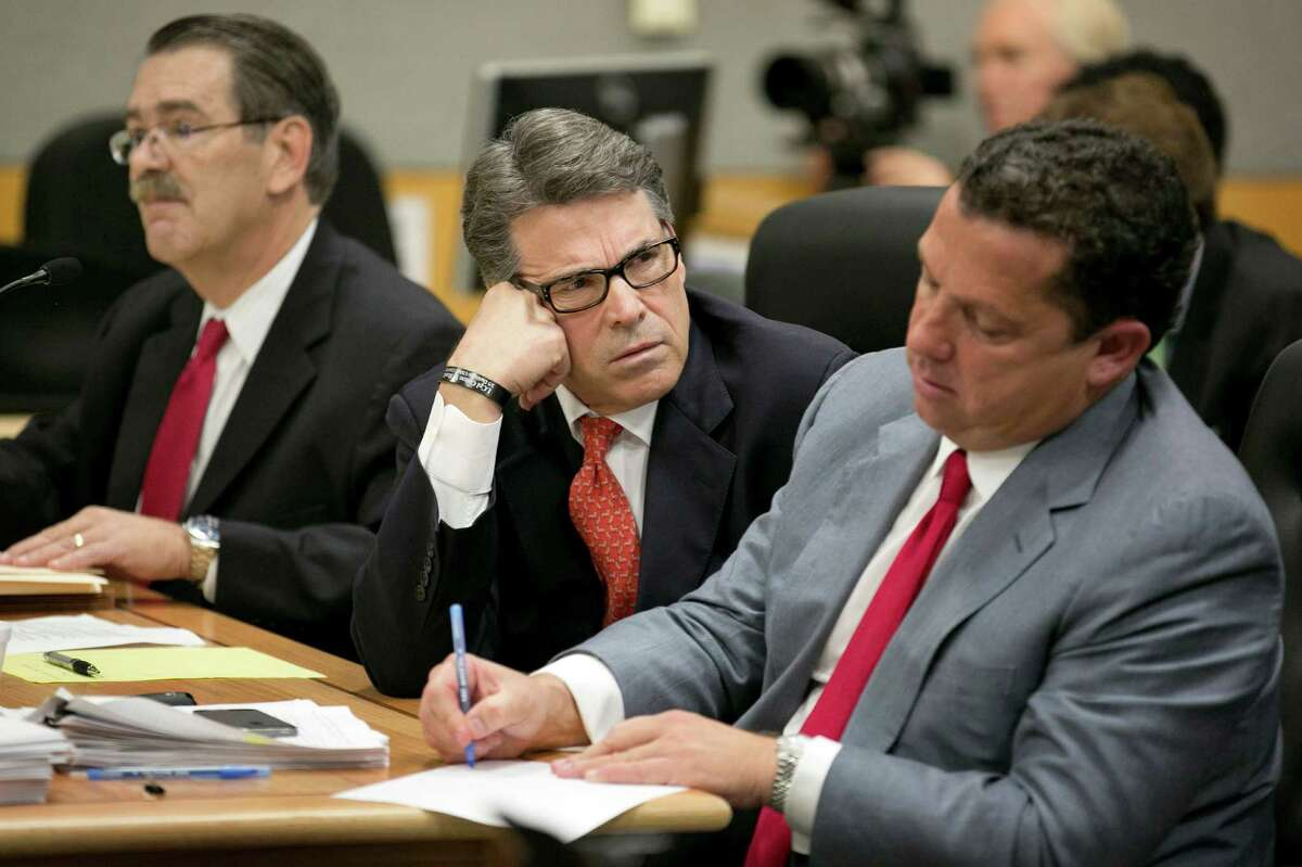 """Gov. Rick Perry, flanked by his lawyers Tony Buzbee, right, and David Botsford, stood by the veto that spurred his indictment on abuse of office charges, saying he'd """"make that veto again."""""""