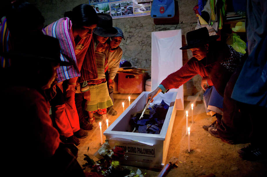 Odelia Gregoria Curo inspects the remains of her brother Hector Curo Palomino during a candle lit wake inside the their home, as is local custom, in Peru's Ayahuanco district. Curo was killed defending the town. Photo: Rodrigo Abd / Associated Press / AP