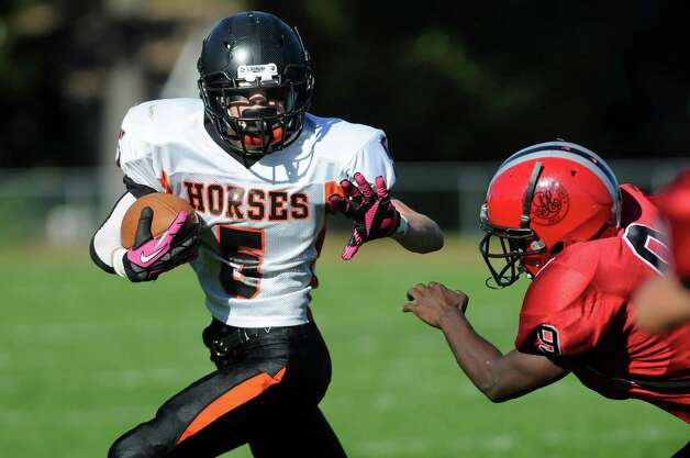 Schuylerville's Zachary Pierce, left, carries the ball as Academy's Zeke Thomas defends during their football game on Friday, Oct. 3, 2014, at Albany Academy in Albany, N.Y. (Cindy Schultz / Times Union) Photo: Cindy Schultz / 00028780A