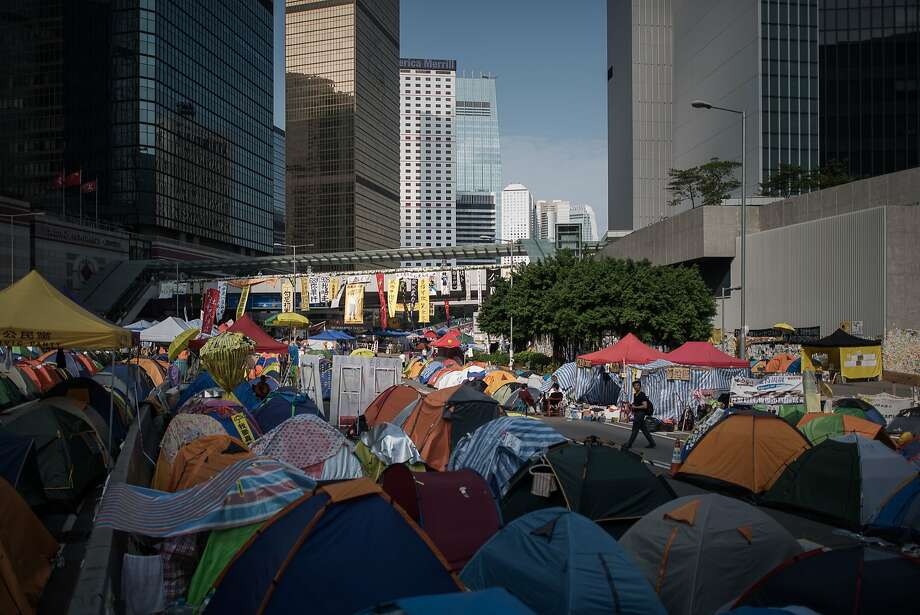A man (right) walks by tents at the encampment of pro-democracy protesters on an occupied highway in the Admiralty district of Hong Kong on November 6, 2014.  More than a month after tens of thousands of Hong Kongers took to the streets demanding free leadership elections for the semi-autonomous Chinese city, weary demonstrators remain encamped across several major roads. Photo: Philippe Lopez, AFP/Getty Images
