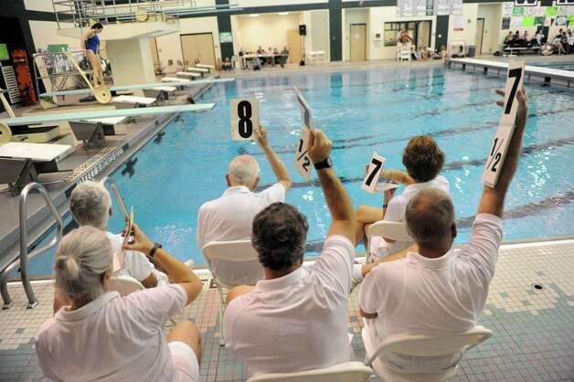 Judges hold up their score cards during the girl's high school Section II diving championships on Thursday Nov. 6, 2014 in Clifton Park, N.Y. (Michael P. Farrell/Times Union) Photo: Michael P. Farrell / 00029394A