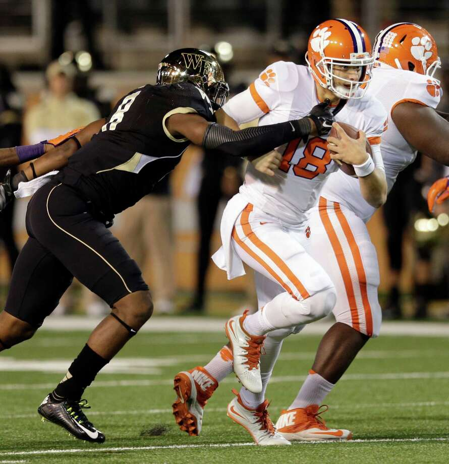 Clemson's Cole Stoudt (18) runs as Wake Forest's Marquel Lee (8) defends during the first half of an NCAA college football game in Winston-Salem, N.C., Thursday, Nov. 6, 2014. (AP Photo/Chuck Burton) ORG XMIT: NCCB105 Photo: Chuck Burton / AP