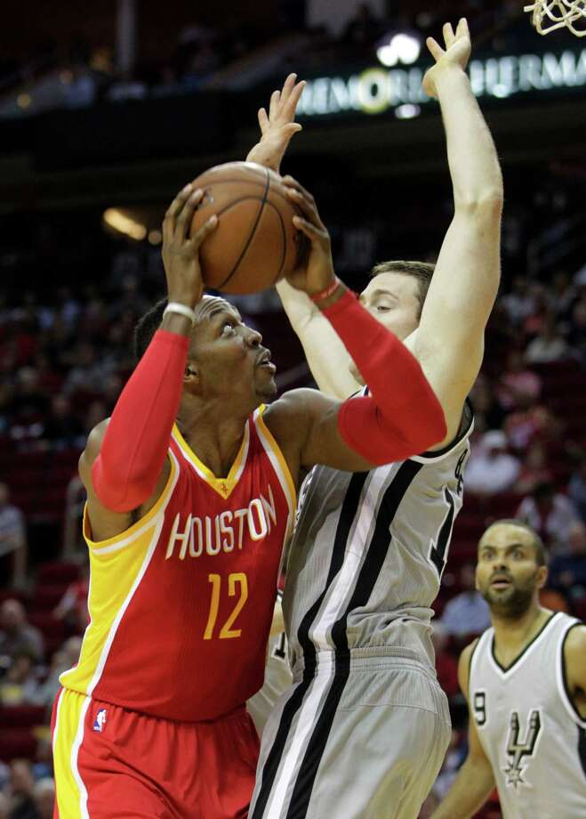 Houston Rockets center Dwight Howard (12) shoots over San Antonio Spurs center Aaron Baynes during the first quarter of an NBA basketball game, Thursday, Nov. 6, 2014, in Houston. (AP Photo/Patric Schneider)  ORG XMIT: TXPX102 Photo: Patric Schneider / FR170473 AP