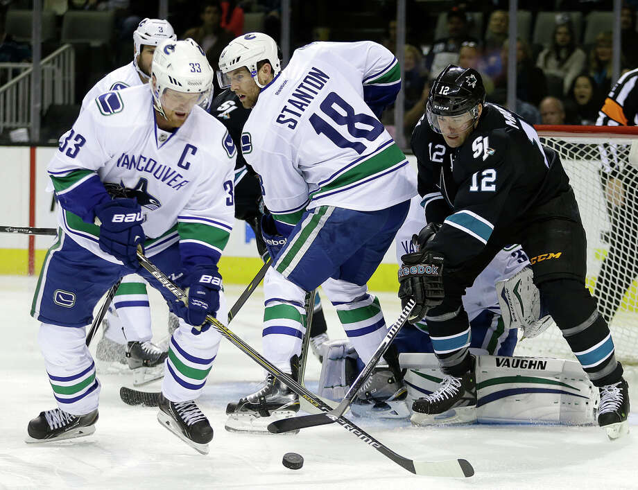 Vancouver Canucks' Henrik Sedin, left, Ryan Stanton (18) and San Jose Sharks' Patrick Marleau, right, fight for the puck during the first period of an NHL hockey game Thursday, Nov. 6, 2014, in San Jose, Calif. (AP Photo/Ben Margot) Photo: Ben Margot / Associated Press / AP