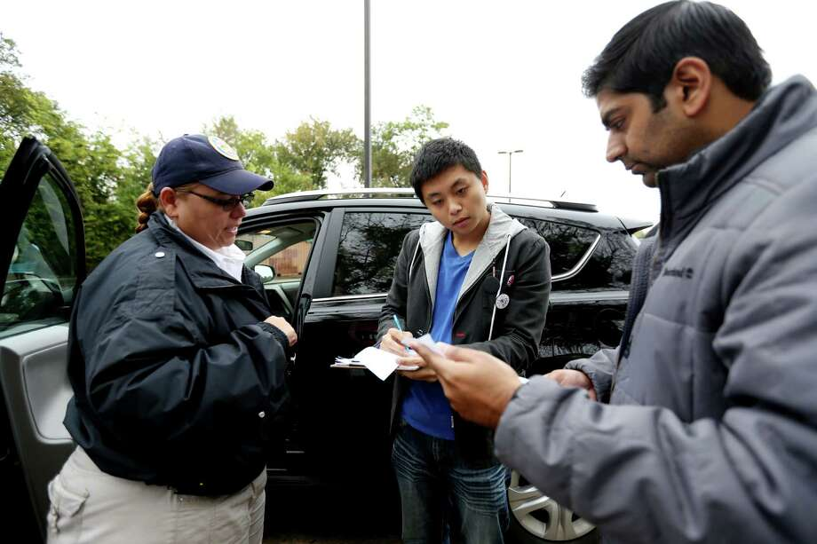 Uber driver partner Chuanqi Lu, 24, center, a recent University of Houston graduate, shown with Irene Aguilar, regulatory investigator of the Houston Administration and Regulatory Affairs Division, and Sarfraz Maredia, general manager for Uber Houston, while getting his vehicle inspected to receive a Transportation Network Company vehicle for hire license permit on Nov. 6, 2014. Photo: Gary Coronado, Houston Chronicle / © 2014 Houston Chronicle
