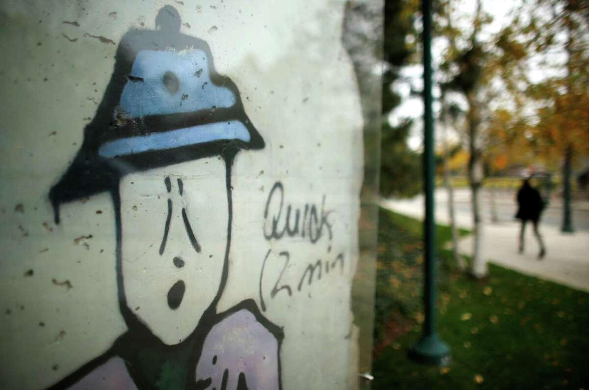 A segment of the Berlin Wall, left, stands outside an EF Education First building, in Cambridge, Mass.