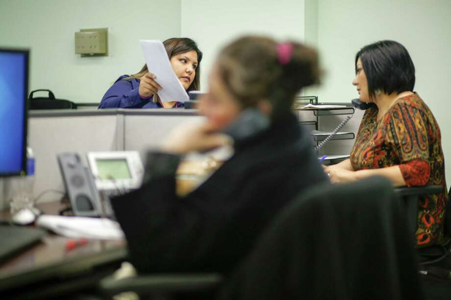 Raquel Rodriguez, left, and Leticia Chaw talk as the Houston Department of Health and Human Services opens its call center to help residents apply for coverage in the health insurance marketplace under the Affordable Care Act. Photo: Eric Kayne, For The Chronicle / Eric Kayne