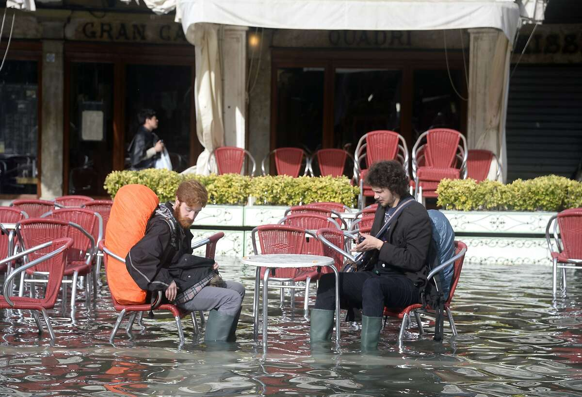They still don't let you sit at a table unless you order a drink: Tourists equipped with high boots sit at a cafe table in St. Mark's Square in Venice after high tides and a strong Scirocco wind in the Adriatic Sea caused flooding. The city of canals has been wrestling with the problems posed by the threat of rising sea levels.