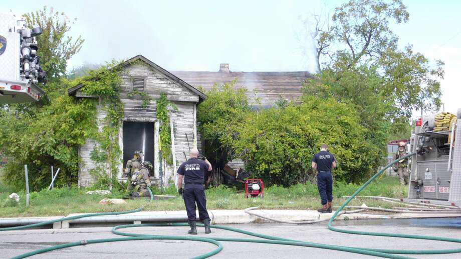 Firefighters respond to a fire at unoccupied home in the 1700 block of East Houston Street. Photo: By John Gonzalez, San Antonio Express-News