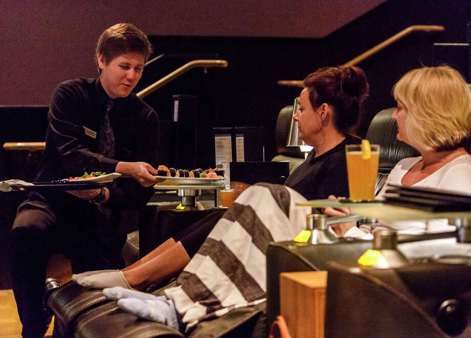 Erik Utermoholen serves sushi rolls to Staci Koran and Cherie Galaviz, who also ordered beer, at Cinepolis Westlake Village luxury cinemas. Photo: Ricardo DeAratanha / McClatchy-Tribune News Service / Los Angeles Times