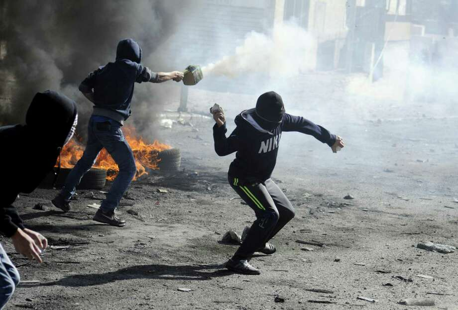 Palestinians throw rocks and shoot fireworks during clashes with Israeli border police, as Israeli police limited the access to Al-Aqsa Mosque in Jerusalem. Photo: Mahmoud Illean / Associated Press / AP