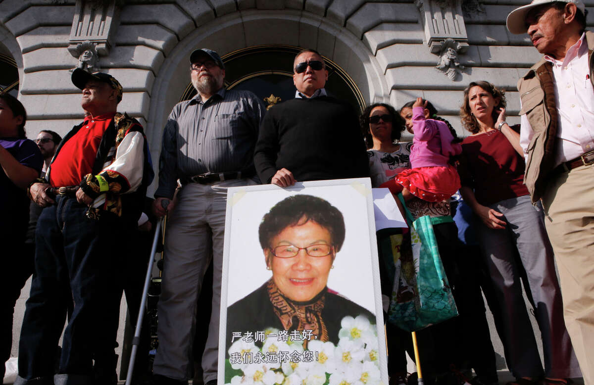 Gene Lee stands behind a photo of his mother, Pui Fong Yim Lee, 78, who was struck by a car and killed in a crosswalk at Stockton and Sacramento streets in Chinatown on Sept. 20.