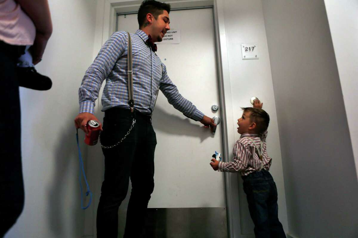 As his father, James, opens the door, James Ceballos, 3, rings the doorbell at their unit in the residential building at 1180 Fourth St. in San Francisco on Nov. 3, 2014.