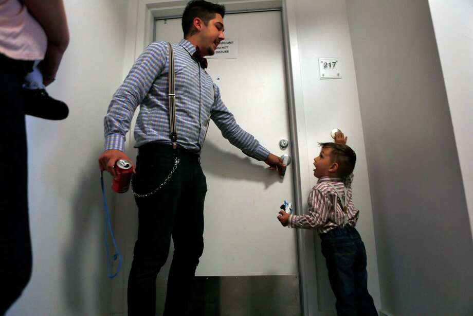 As his father, James, opens the door, James Ceballos, 3, rings the doorbell at their unit in the residential building at 1180 Fourth St. in San Francisco on Nov. 3, 2014. Photo: Scott Strazzante / The Chronicle / ONLINE_YES
