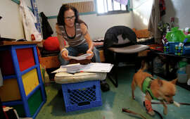 Laura Martinez looks over her recent housing applications inside her room at the homeless shelter while her dog Peanut retrieves his bone.