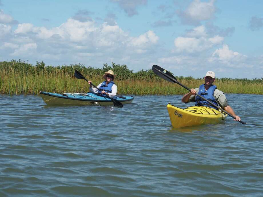 Pam LeBlanc, left, and guide Alan Raby, right, paddle kayaks along the Port O'Connor Paddling Trail. Photo: Chris LeBlanc, Special To The Statesman / Austin American-Statesman