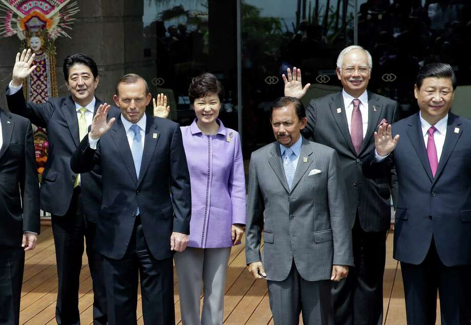 FILE - In this Oct. 8, 2013 file photo, Chinese President Xi Jinping, right, and Japanese Prime Minister Shinzo Abe, left, wave with other leaders of the Asia-Pacific region, from second left, Australian Prime Minister Tony Abbott, South Korean President Park Geun-hye, Brunei Sultan Hassanal Bolkiah and Malaysian Prime Minister Najib Razak, as they stand for a group photo session during the Asia-Pacific Economic Cooperation (APEC) forum in Bali, Indonesia. China said Friday, Nov. 7, 2014, it reached agreement with Japan to ramp up high-level contacts, the strongest indication yet of a possible meeting between Xi and Abe at next week's Asia-Pacific Economic Cooperation summit. (AP Photo/Dita Alangkara, File) Photo: Dita Alangkara / Associated Press / AP