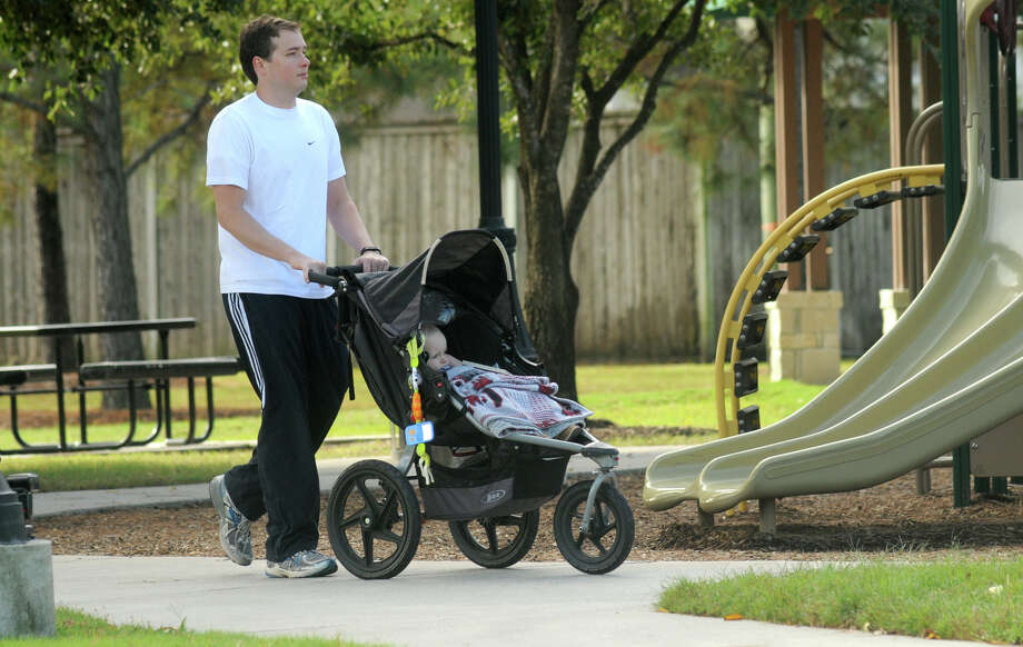 Sam McQuillin, 29, logs steps on his Fitbit by pushing son Walker, 17 months, in his stroller at a park near his home. McQuillin's daily goal is at least 10,000 steps. Photo: Jerry Baker, Freelance