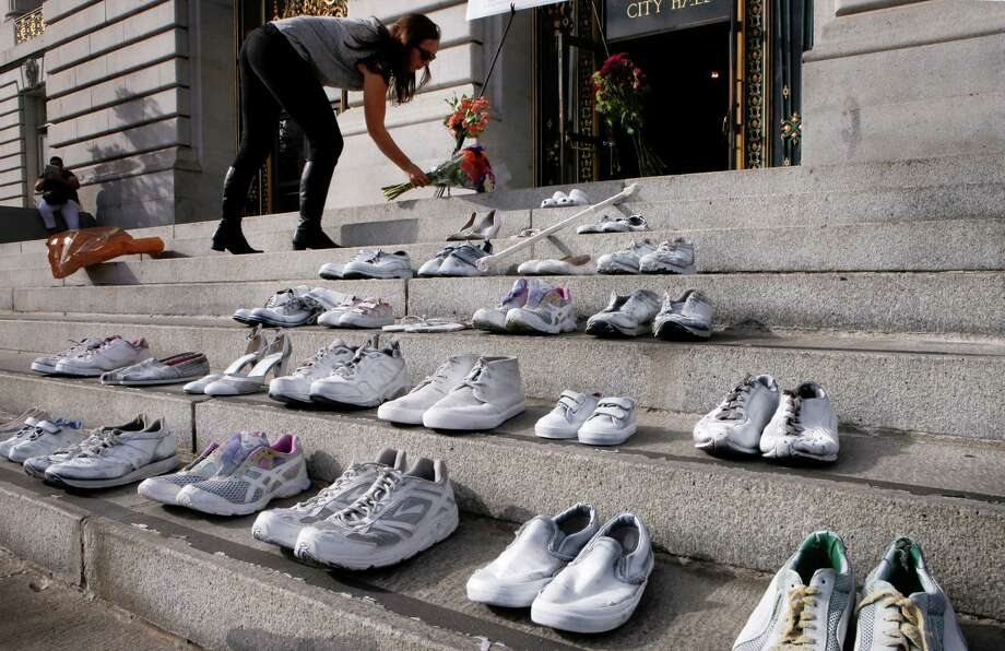 Tyler Frisbee with the SF Bicycle Coalition, on Friday Nov. 7, 2014, places flowers on the steps of City Hall where twenty eight pairs of shoes were placed to represent the lives lost during the year to traffic related incidents. Members of San Francisco's Vision Zero Coalition gathered in San Francisco, Calif. to draw attention to the alarming increase of traffic related deaths on the the streets of the city in 2014. Photo: Michael Macor / The Chronicle / ONLINE_YES