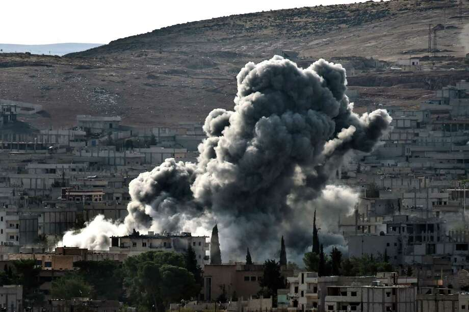 Smoke rises from the Syrian town of Ain al-Arab, known as Kobane by the Kurds, after a US-led coalition strike as seen from the Turkish-Syrian border in the southeastern village of Mursitpinar in the Sanliurfa province on October 15, 2014. US-led aircraft will continue bombing near the Syrian town of Ain al-Arab (Kobane) and in western Iraq, President Barack Obama said after talks with military leaders from an international coalition fighting the Islamic State group. AFP PHOTO / ARIS MESSINISARIS MESSINIS/AFP/Getty Images Photo: ARIS MESSINIS / AFP