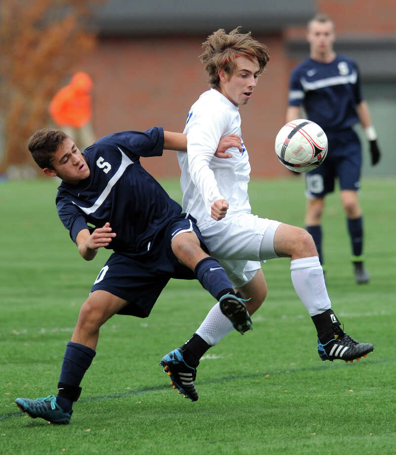 Darien's Jack Kniffin (in white) controls the ball ahead of Staples' Gabe Pensak during the Class LL boys soccer state quarterfinal game at Darien High School, Nov. 7, 2014. Darien won the game 2-0. Photo: Ned Gerard / Connecticut Post