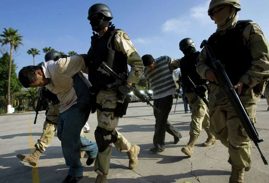 Mexican soldiers arrest two drug-smuggling suspects in Tijuana. A reader says the only solution to the drug scourge is to legalize the drugs the gangs smuggle into the United States. Photo: Guillermo Arias / Guillermo Arias / Associated Press / AP