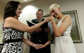 Sen. Jim Dabakis marries Yolanda Pascua (left) and Laekin Rogers as she wipes away tears on Oct. 6, 2014, at the Salt Lake County Complex. The U.S. Supreme Court declined to review all five pending same-sex marriage cases, effectively legalizing gay and lesbian unions and clearing the way for such marriages to proceed in 11 new states, including Utah.