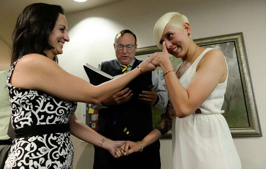 Sen. Jim Dabakis marries Yolanda Pascua (left) and Laekin Rogers as she wipes away tears on Oct. 6, 2014, at the Salt Lake County Complex. The U.S. Supreme Court declined to review all five pending same-sex marriage cases, effectively legalizing gay and lesbian unions and clearing the way for such marriages to proceed in 11 new states, including Utah. Photo: Francisco Kjolseth / Associated Press / The Salt Lake Tribune