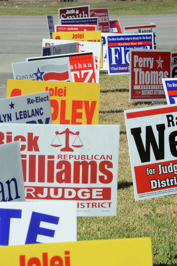 Traffic drives past dozens of election signs at the Theodore R Johns Sr Library on Friday. Early voting will continue through October 31. Photo taken Friday, October 24, 2014 Guiseppe Barranco/@spotnewsshooter Photo: Guiseppe Barranco, Photo Editor