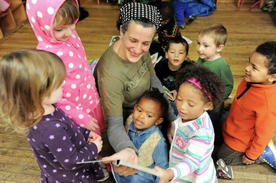 Preschool teacher Andre Castagneto, center, reads a story to her charges before going outside to play on Wednesday, Nov. 5, 2014, at The Free School in Albany, N.Y. (Cindy Schultz / Times Union) Photo: Cindy Schultz / 00029346A