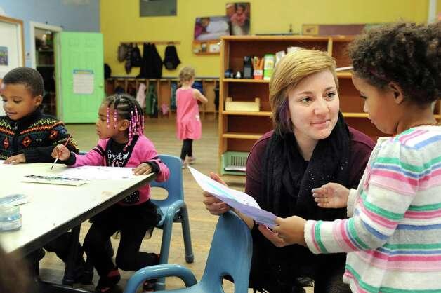 Preschooler Natane Moore-Muncada, 3, right, shows her artwork to intern Sophia DeVito on Wednesday, Nov. 5, 2014, at The Free School in Albany, N.Y. (Cindy Schultz / Times Union) Photo: Cindy Schultz / 00029346A