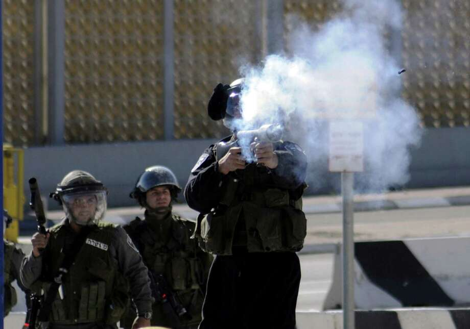 An Israeli border policeman shoots a rubber-coated bullet during clashes with Palestinians, as Israeli police limited the access to Al-Aqsa Mosque in Jerusalem on Friday, Nov. 7, 2014. Tensions have been rising in recent weeks over the Jerusalem shrine, known to Muslims as Haram al-Sharif, or Noble Sanctuary, and to Jews as the Temple Mount. (AP Photo/Mahmoud Illean) Photo: Mahmoud Illean, STR / AP